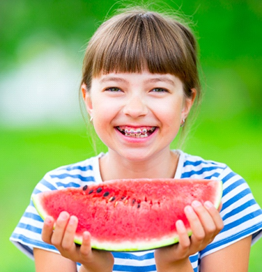 A young girl wearing a striped shirt and smiling with braces preparing to eat a slice of watermelon