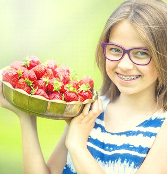 A young girl with purple glasses holding a bowl full of strawberries and smiling while outdoors