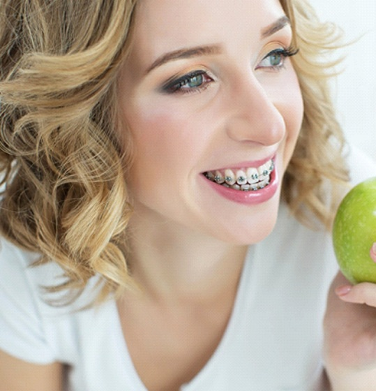 A young woman with braces holding a full apple in her hand