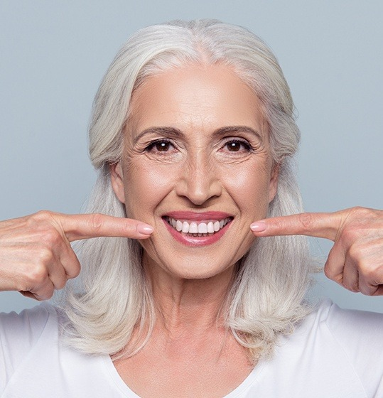 Woman pointing to smile after full mouth reconstruction