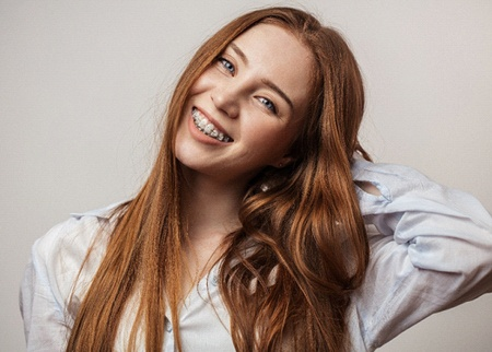 smiling young woman with clear/ceramic braces in Denison