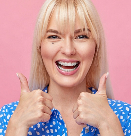 excited woman giving thumbs up for clear braces