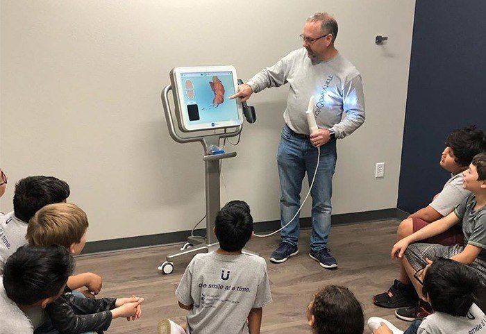 Dentist showing kids an image on the computer screen