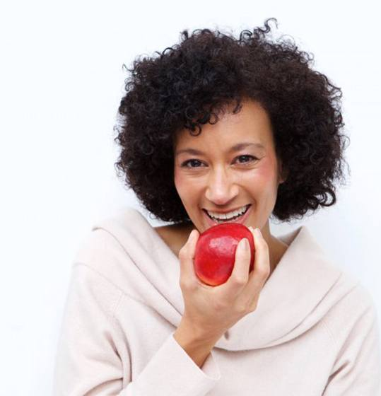 woman biting into red apple