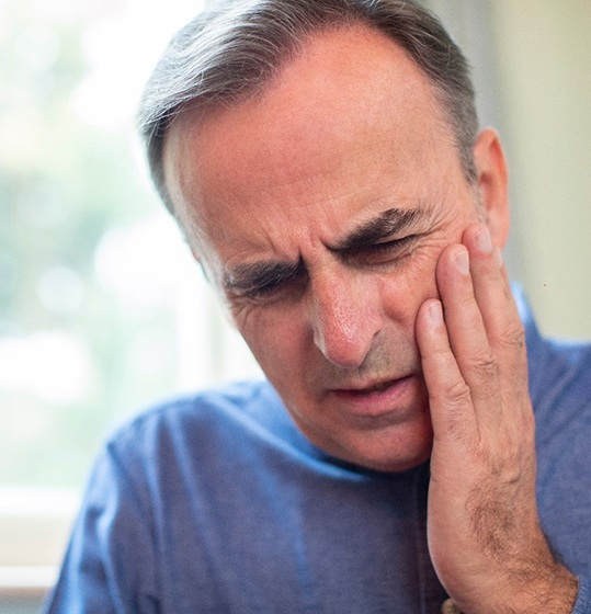 Older man with tooth pain rubbing his jaw