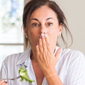 Woman with lost filling covering her mouth