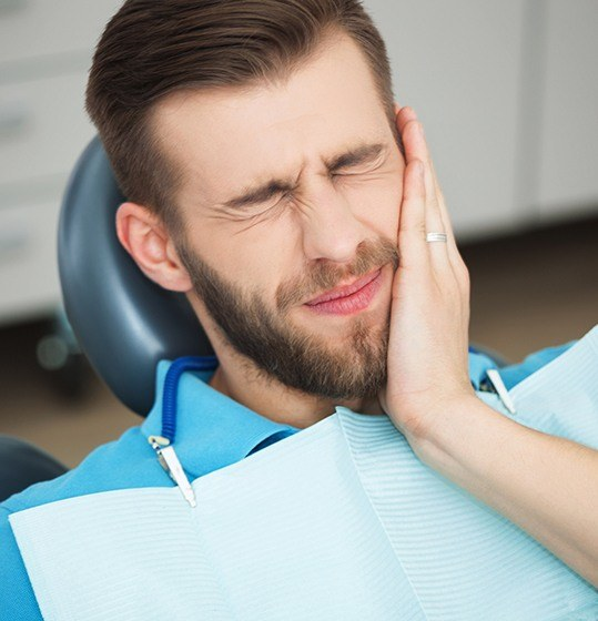 Man holding cheek during emergency dentistry visit