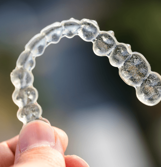 Hand holding a clear Invisalign tray