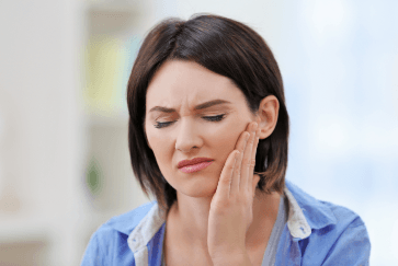 Woman in need of restortive dentistry holding jaw