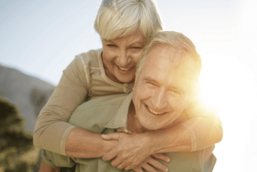 Older man and woman with healthy smiles after periodontal therapy